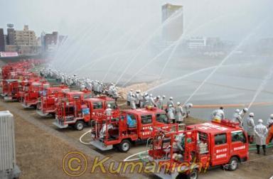 消防出初め式で一斉放水=熊本市 熊本市の消防出初め式で一斉放水する消防団員ら=熊本市の白川河川敷